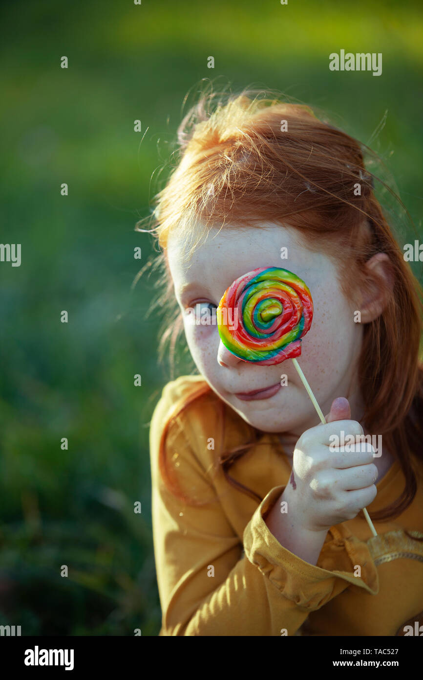 Grimacing girl covering her eye with a lollipop - Stock Image