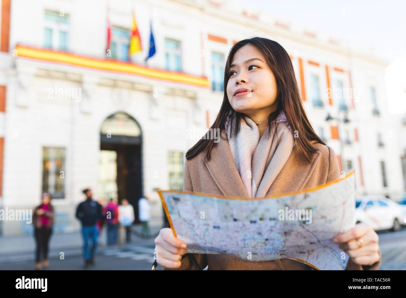 Spain, Madrid, young woman with map exploring the city - Stock Image
