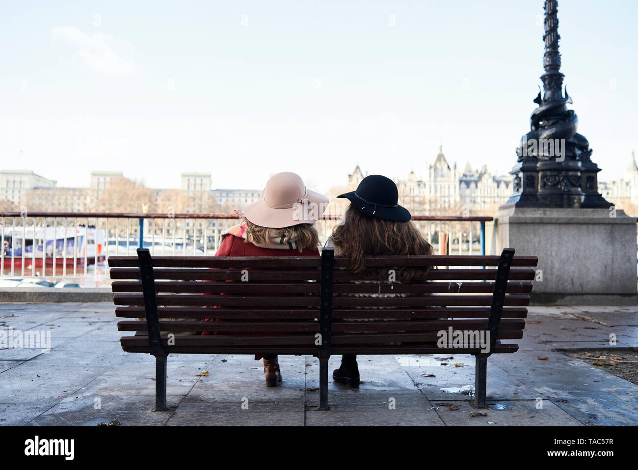 UK, London, rear view of two women sitting on a bench at River Thames promenade Stock Photo