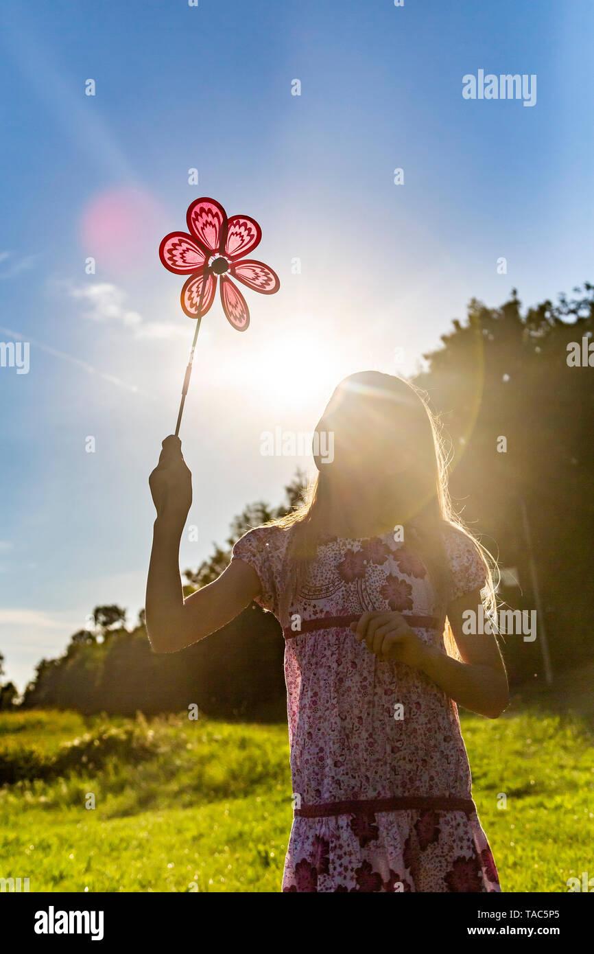 Girl standing on summer meadow looking at pinwheel - Stock Image