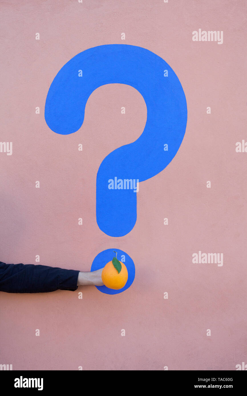 Man's hand holding an orange at a wall with question mark - Stock Image