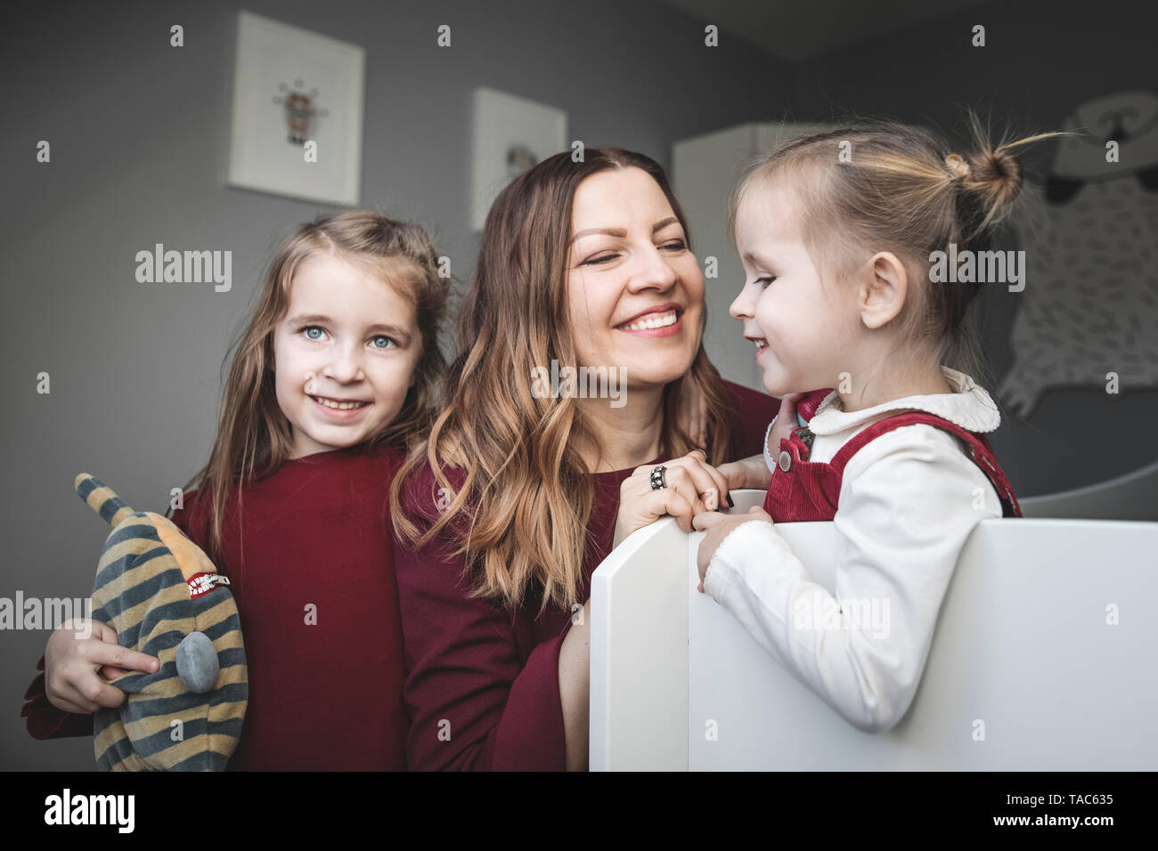 Happy mother with two girls at home - Stock Image