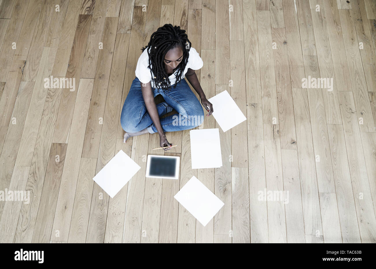 Woman sitting on the floor with digital tablet and blank sheets of paper Stock Photo