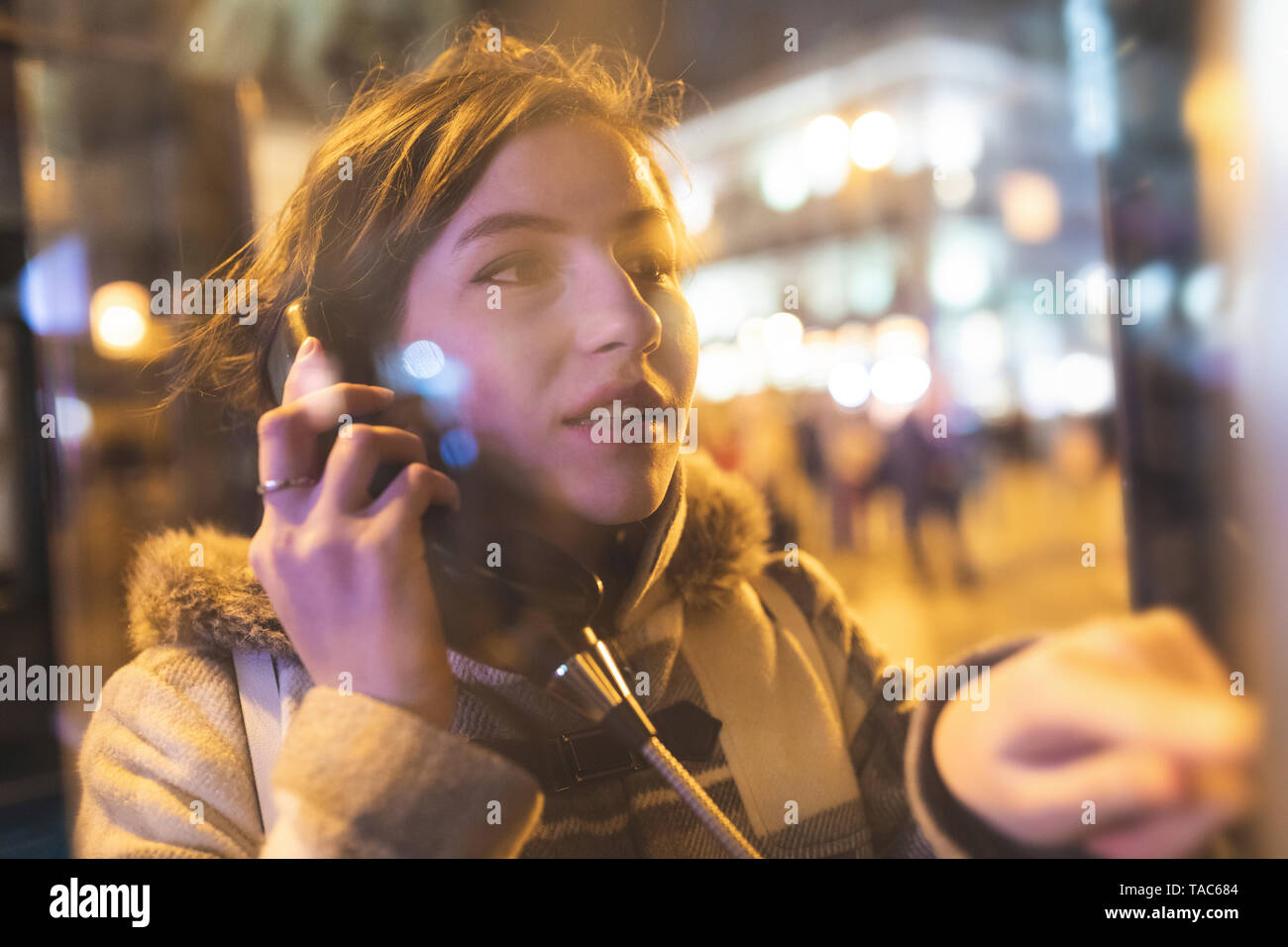 Spain, Madrid, young woman in the city using a phone box - Stock Image
