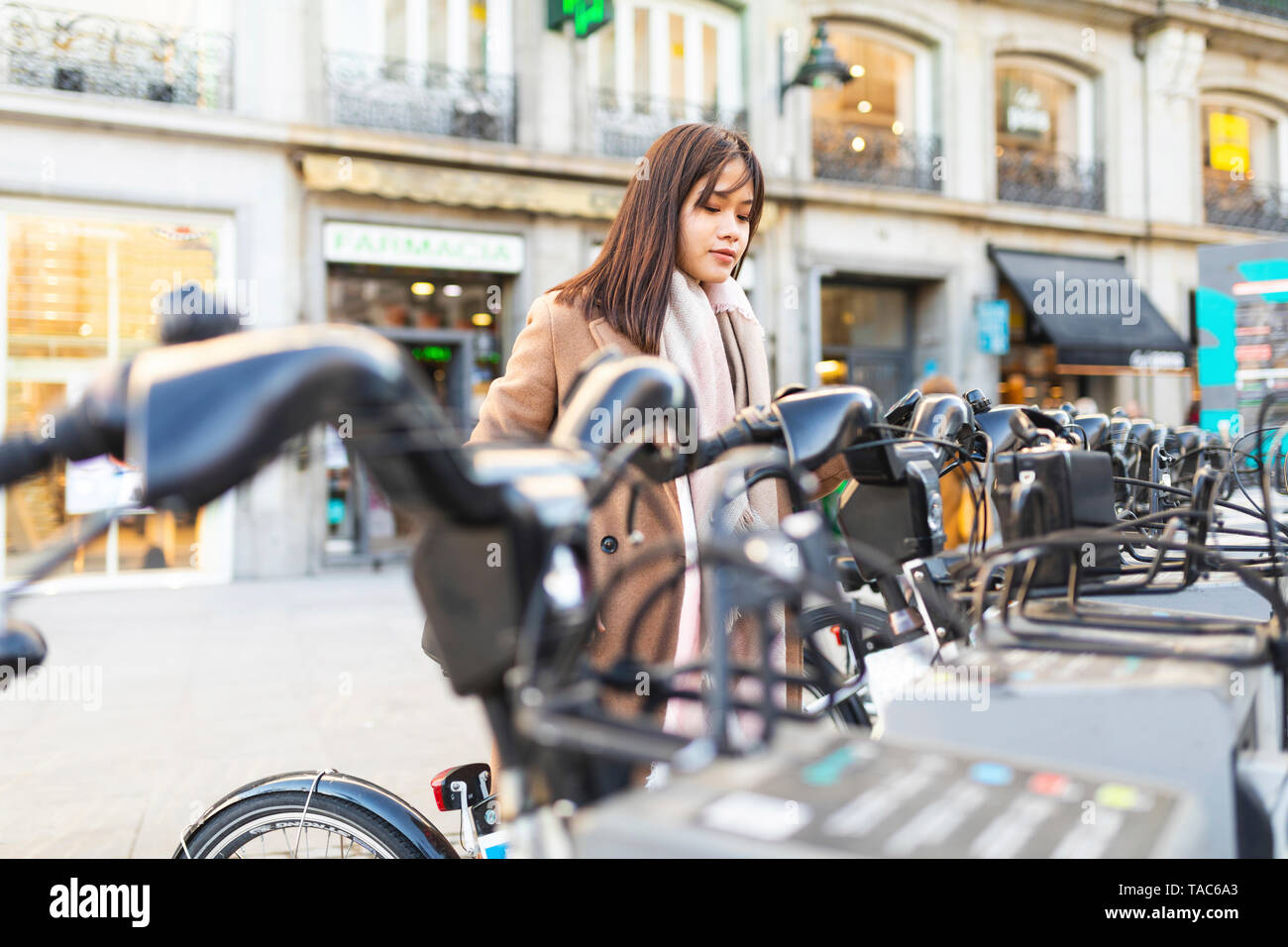 Spain, Madrid, young woman using rental bike in the city - Stock Image