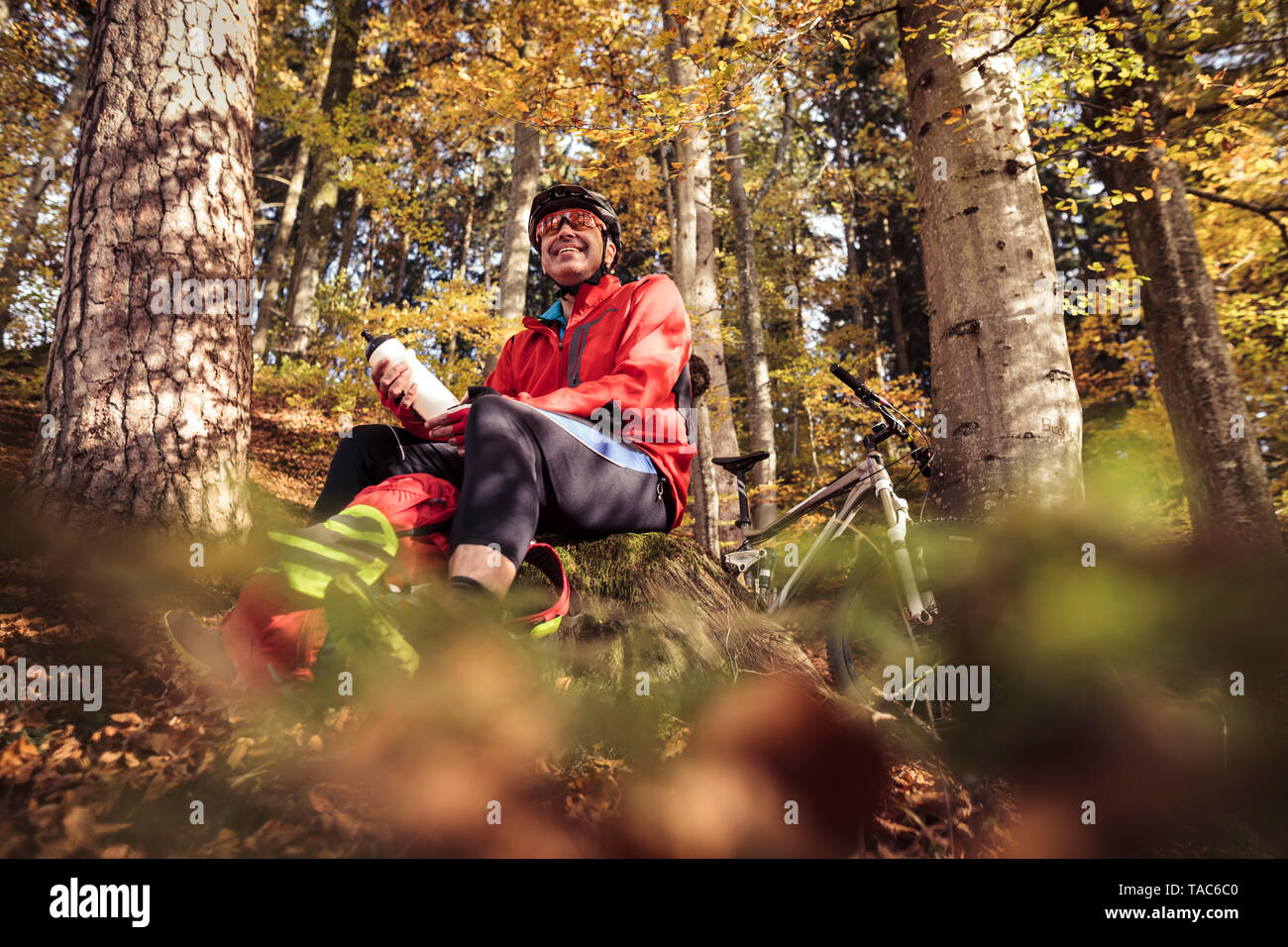 Man with mountainbike having a break in forest Stock Photo