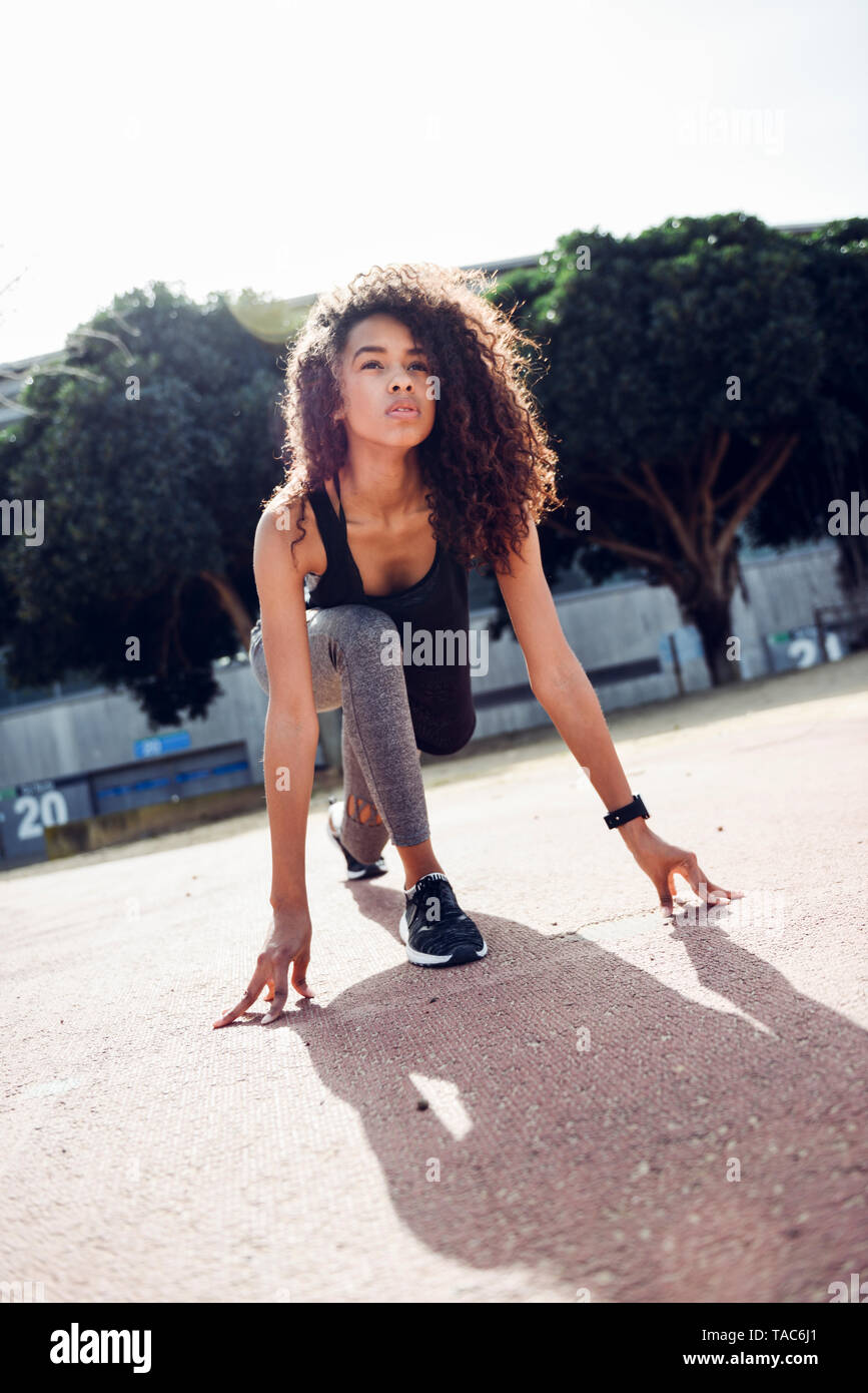 Sporty young woman on tartan track starting Stock Photo