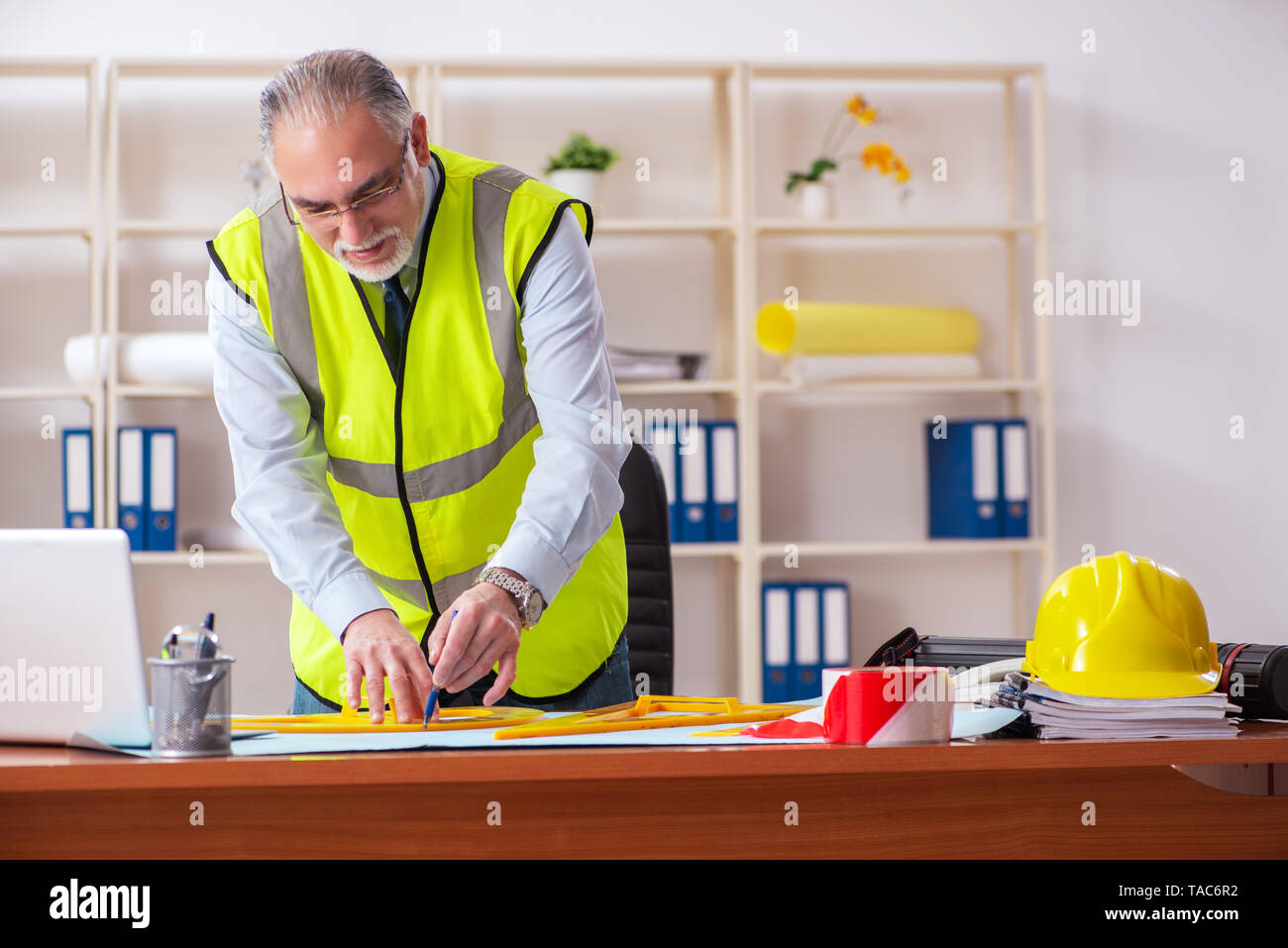 Aged construction engineer working in the office - Stock Image