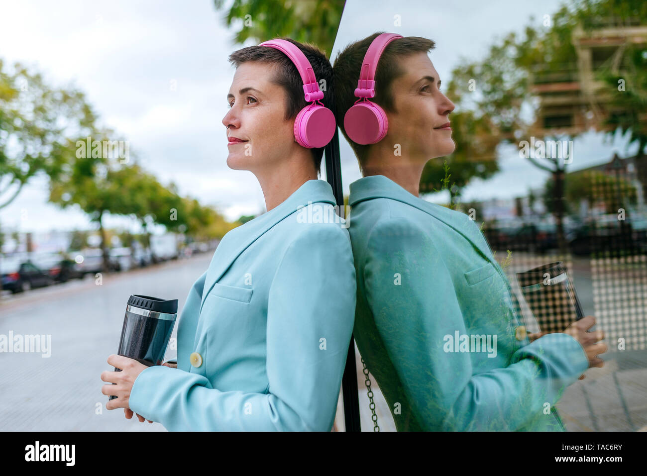 Woman dressed in jacket with thermo mug and pink headphones, reflection - Stock Image