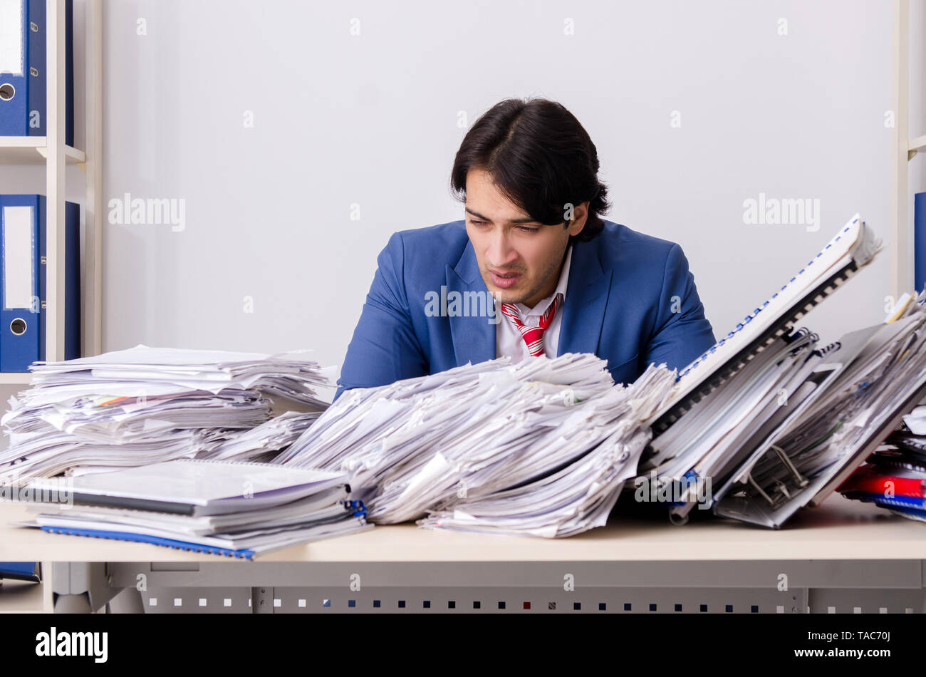 Young businessman employee unhappy with excessive work - Stock Image