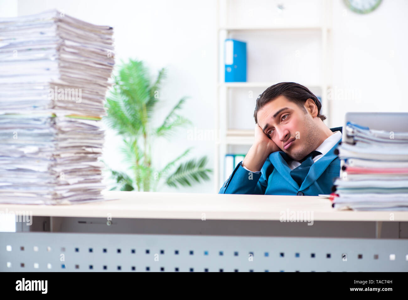 Young male employee unhappy with excessive work - Stock Image