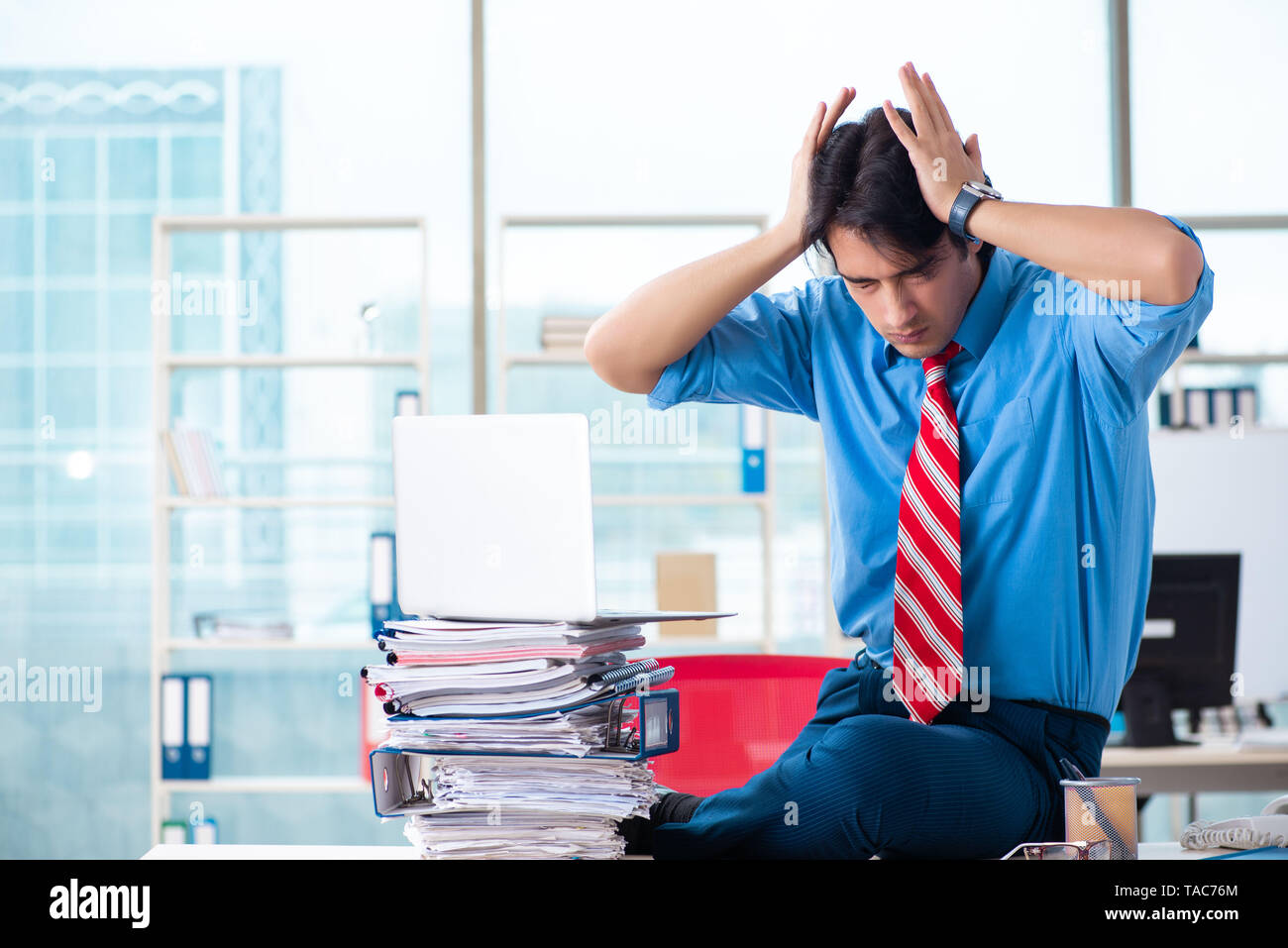 Handsome businessman unhappy with excessive work in the office - Stock Image