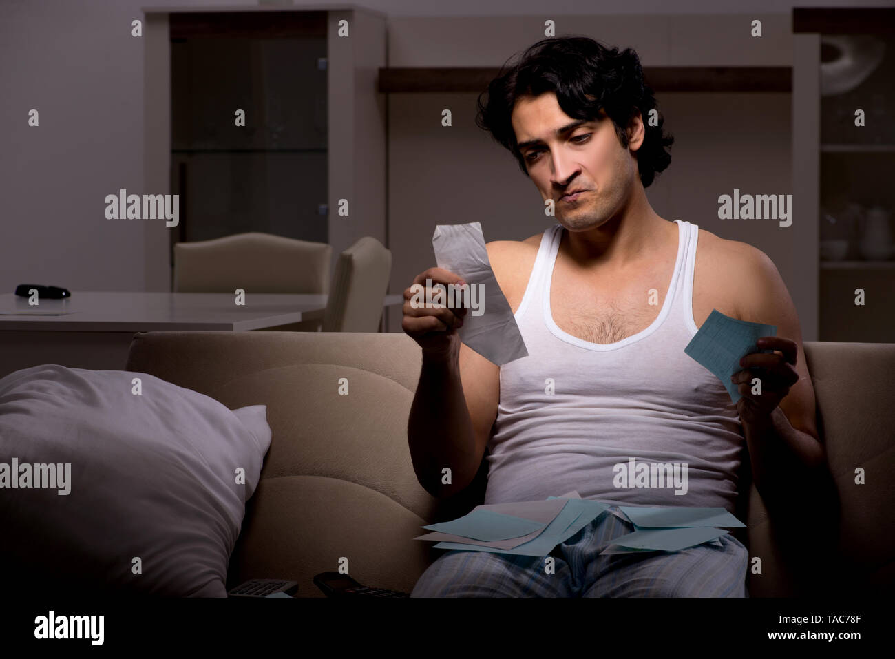Young man calculating expences night at home - Stock Image