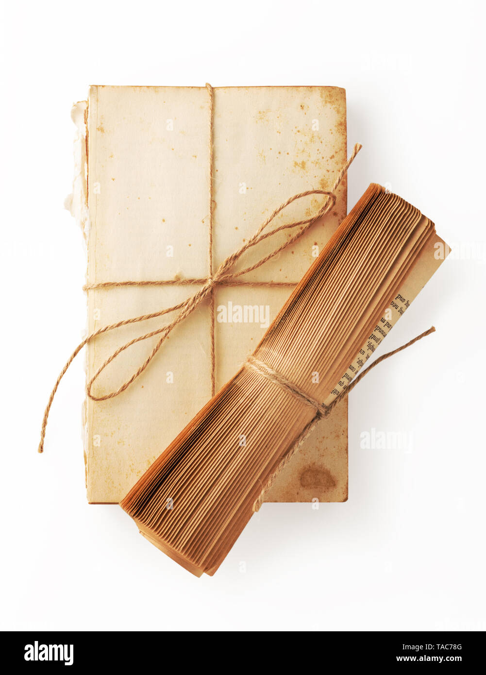 Viintage book paper roll on ripped old book with brown string tied on white background - Stock Image