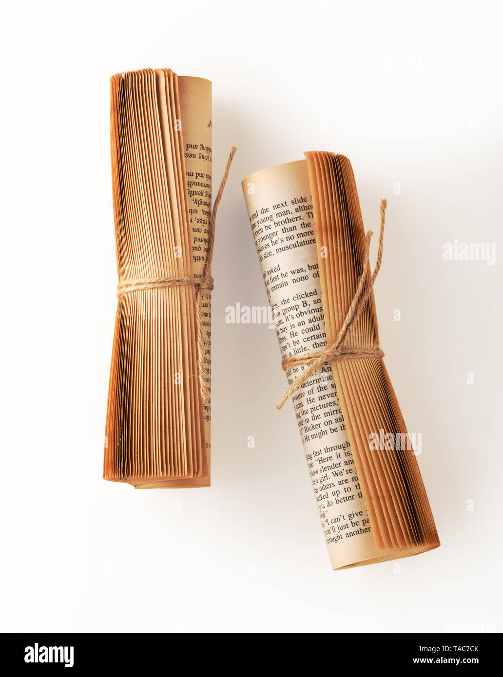 Old book paper roll with brown string tied, vintage book decor on white background - Stock Image