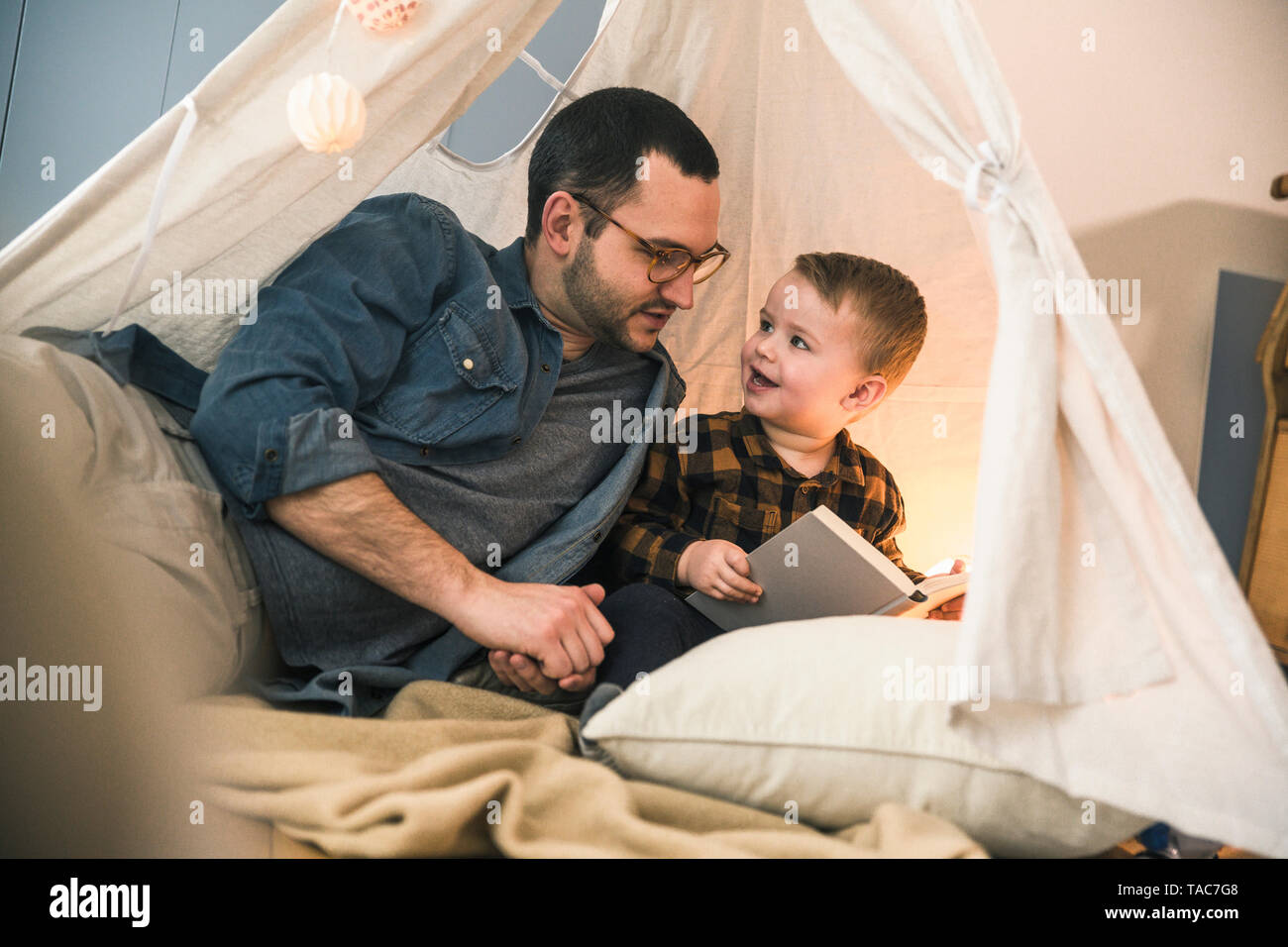 Father and son reading a book together in tent at home - Stock Image
