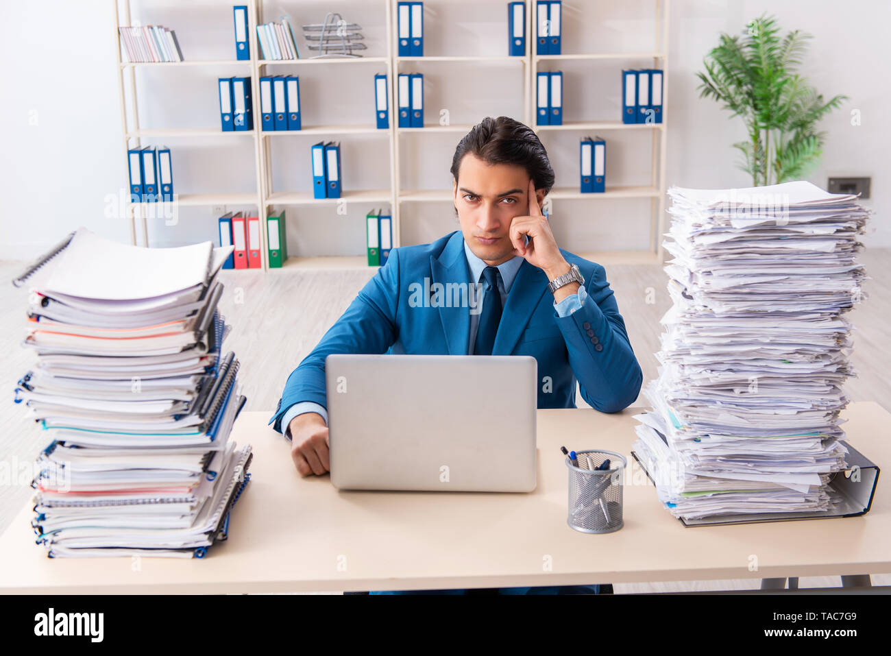 Young handsome businessman unhappy with excessive work - Stock Image