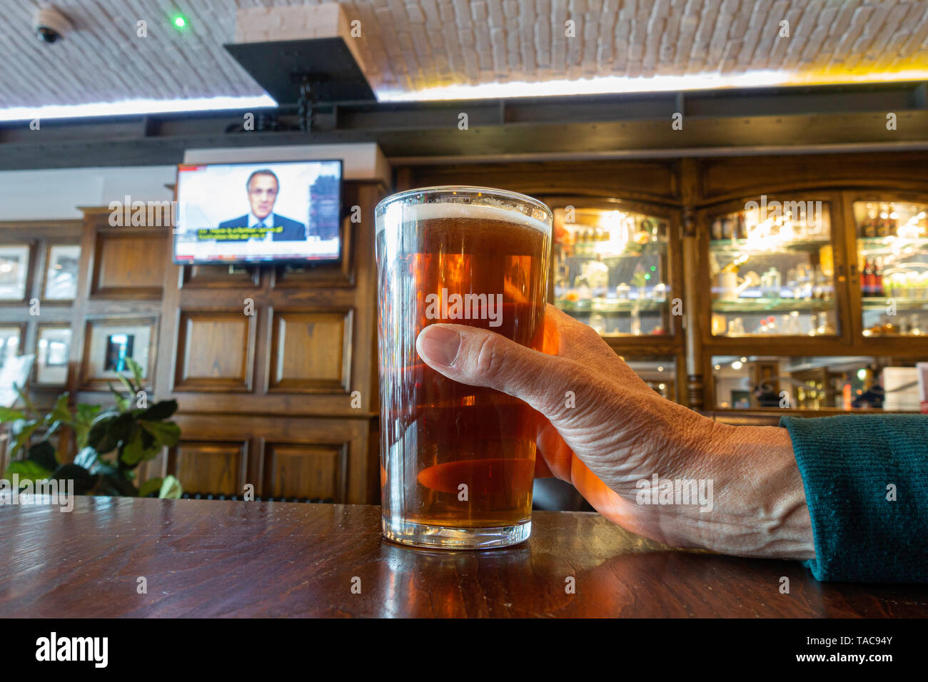 Person holding pint of craft beer in pub with news on TV in background. UK - Stock Image