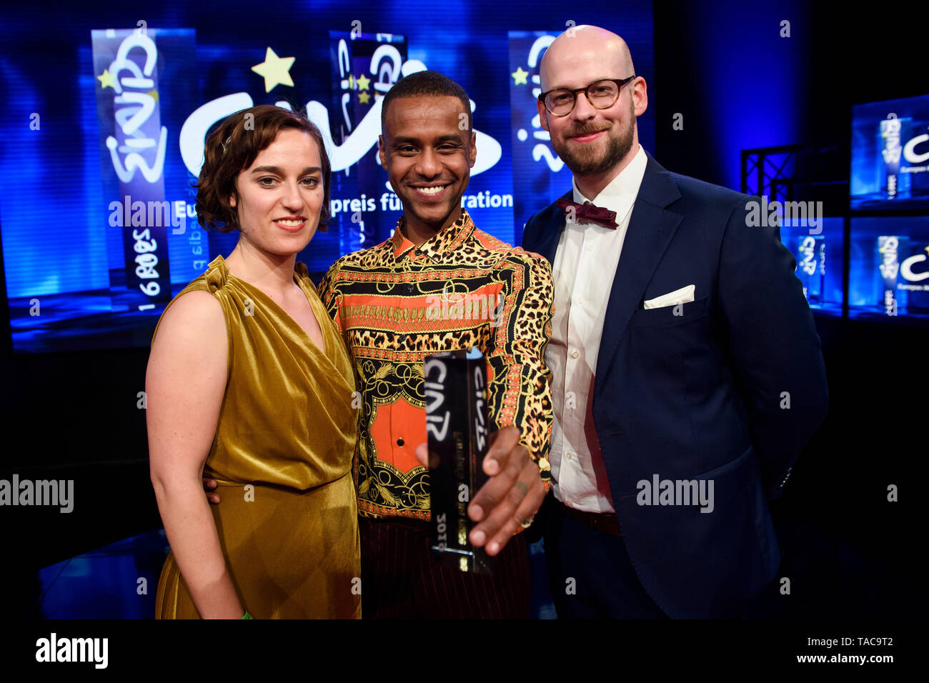 """Berlin, Germany. 23rd May, 2019. Mirjam Wlodawer, Tarik Tesfu, and Nicolas de Leval Jezierski, winner of the CIVIS Media Prize for their web video Jäger & Sammler: Stadt. Country. home,"""" stand on stage with their prize in their hand. The CIVIS Media Prize is awarded for the 32nd time and honours European programme achievements in the field of migration, integration and cultural diversity. Credit: Gregor Fischer/dpa/Alamy Live News Stock Photo"""