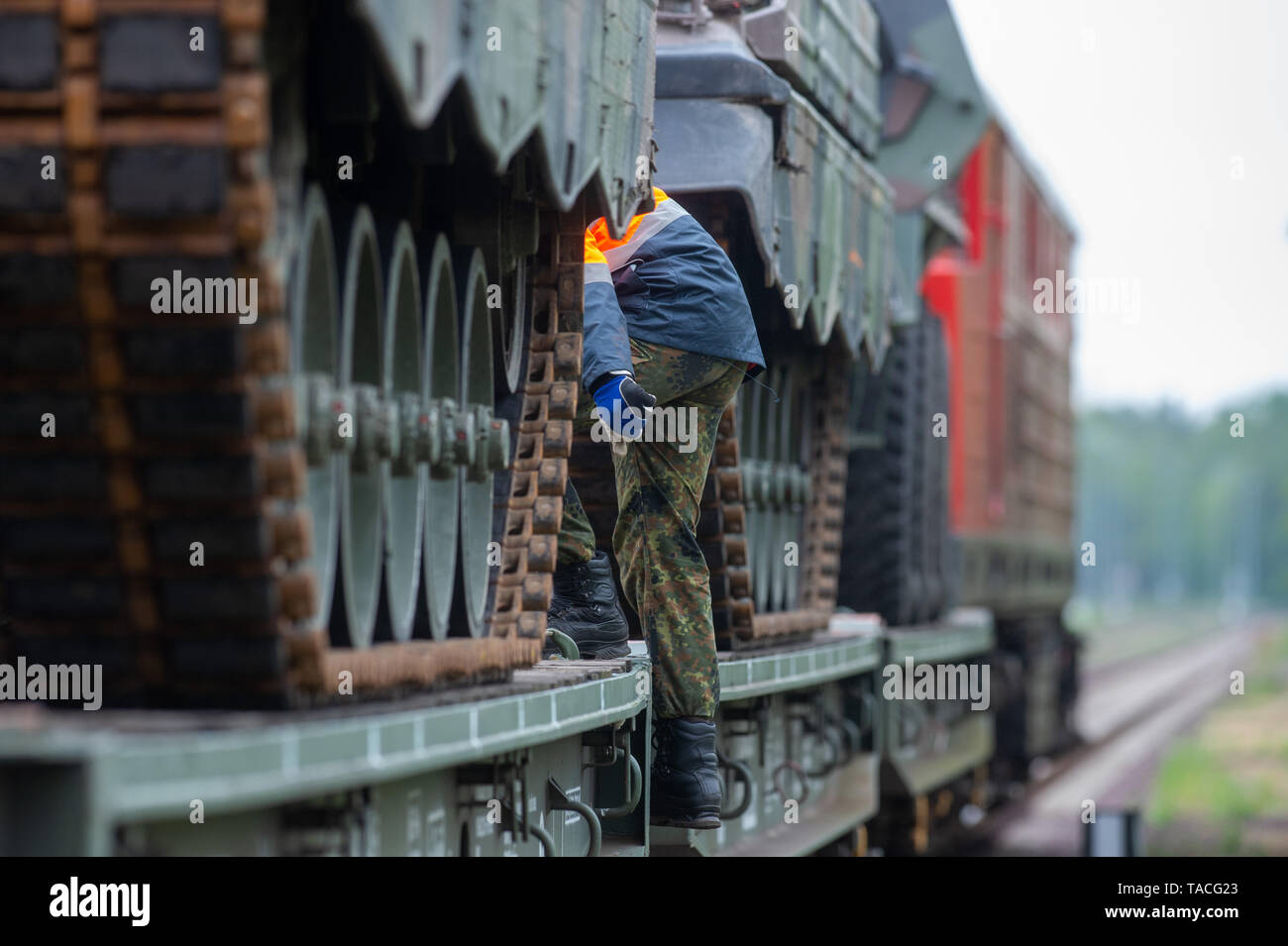 Altengrabow, Germany. 22nd May, 2019. A soldier from Logistics Battalion 171 'Saxony-Anhalt' climbs onto a wagon on which tracked vehicles were transported. The unloading of the train was part of a battalion field exercise. 600 soldiers took part in the exercise which began on 13 May 2019 and will continue until 24 May 2019. Credit: Klaus-Dietmar Gabbert/dpa-Zentralbild/ZB/dpa/Alamy Live News - Stock Image