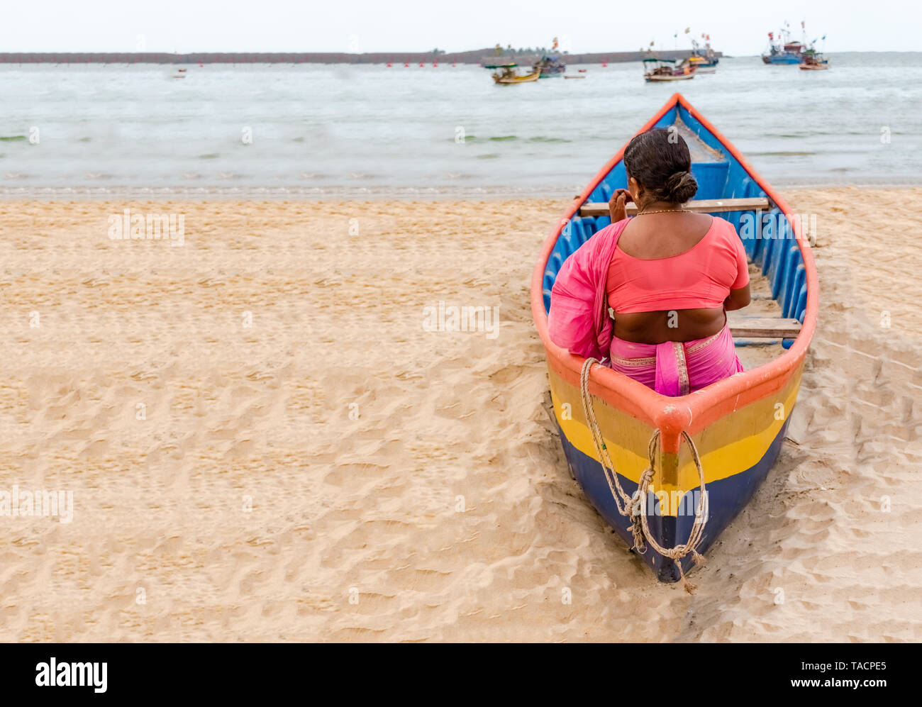 Indian Woman, wearing Ethnic Saree in Marathi style, waiting in colorful canoe, for her husband to return from fishing. Space in left for writing text - Stock Image