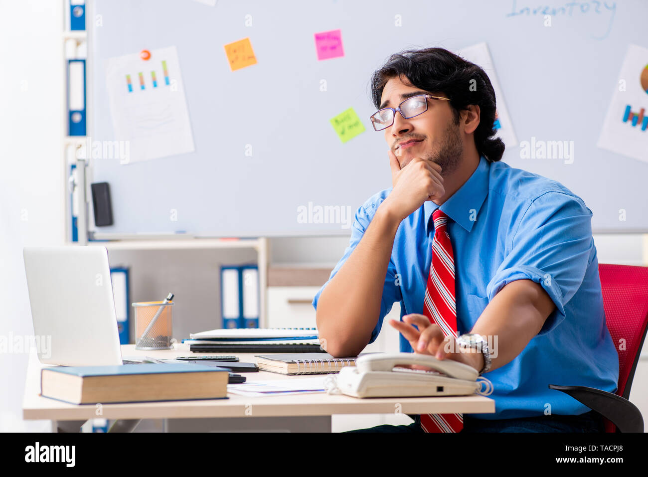 Young male financial manager working in the office - Stock Image