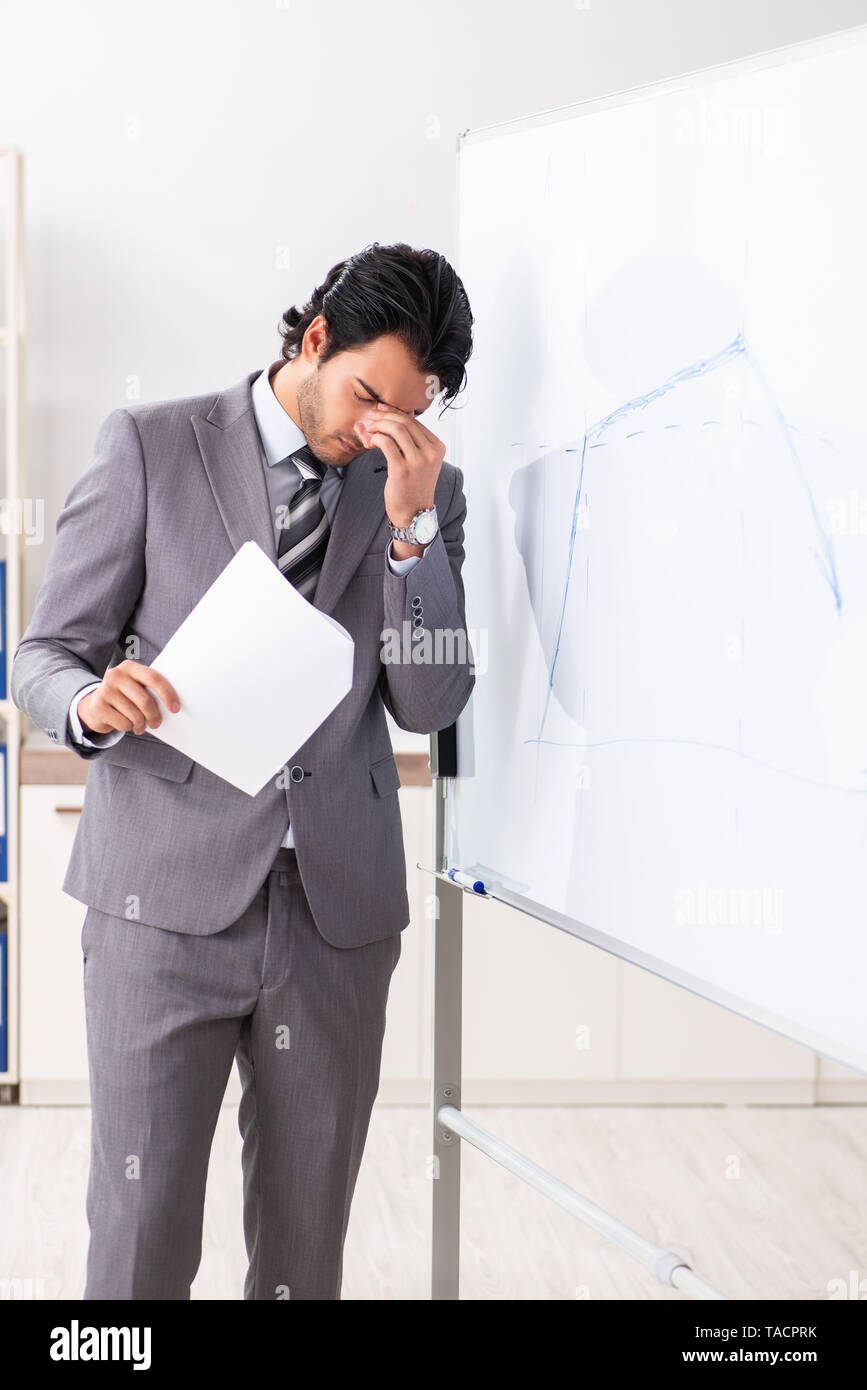 Young handsome businessman in front of whiteboard - Stock Image