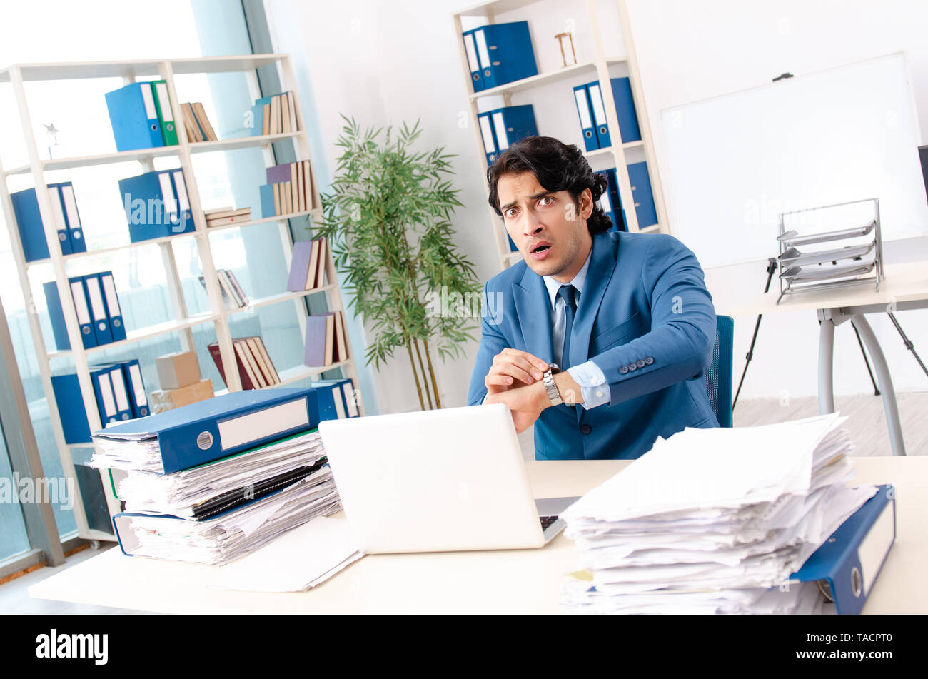 Young handsome male employee with too much work in the office - Stock Image