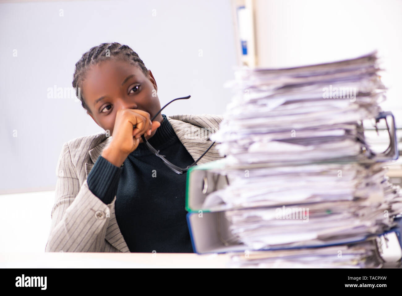 Black female employee unhappy with excessive work - Stock Image