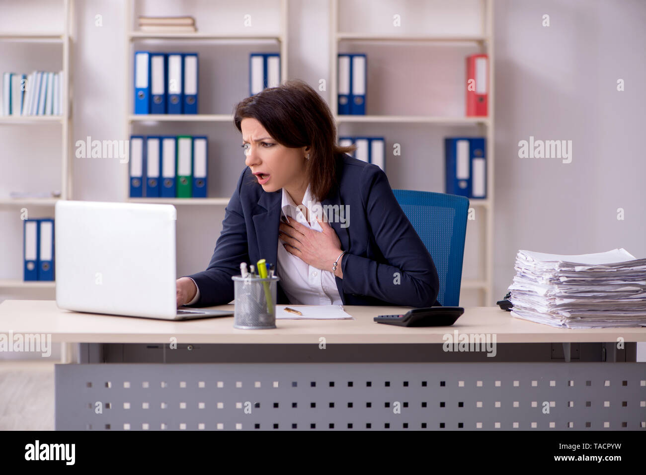 Middle-aged female employee suffering in the office - Stock Image