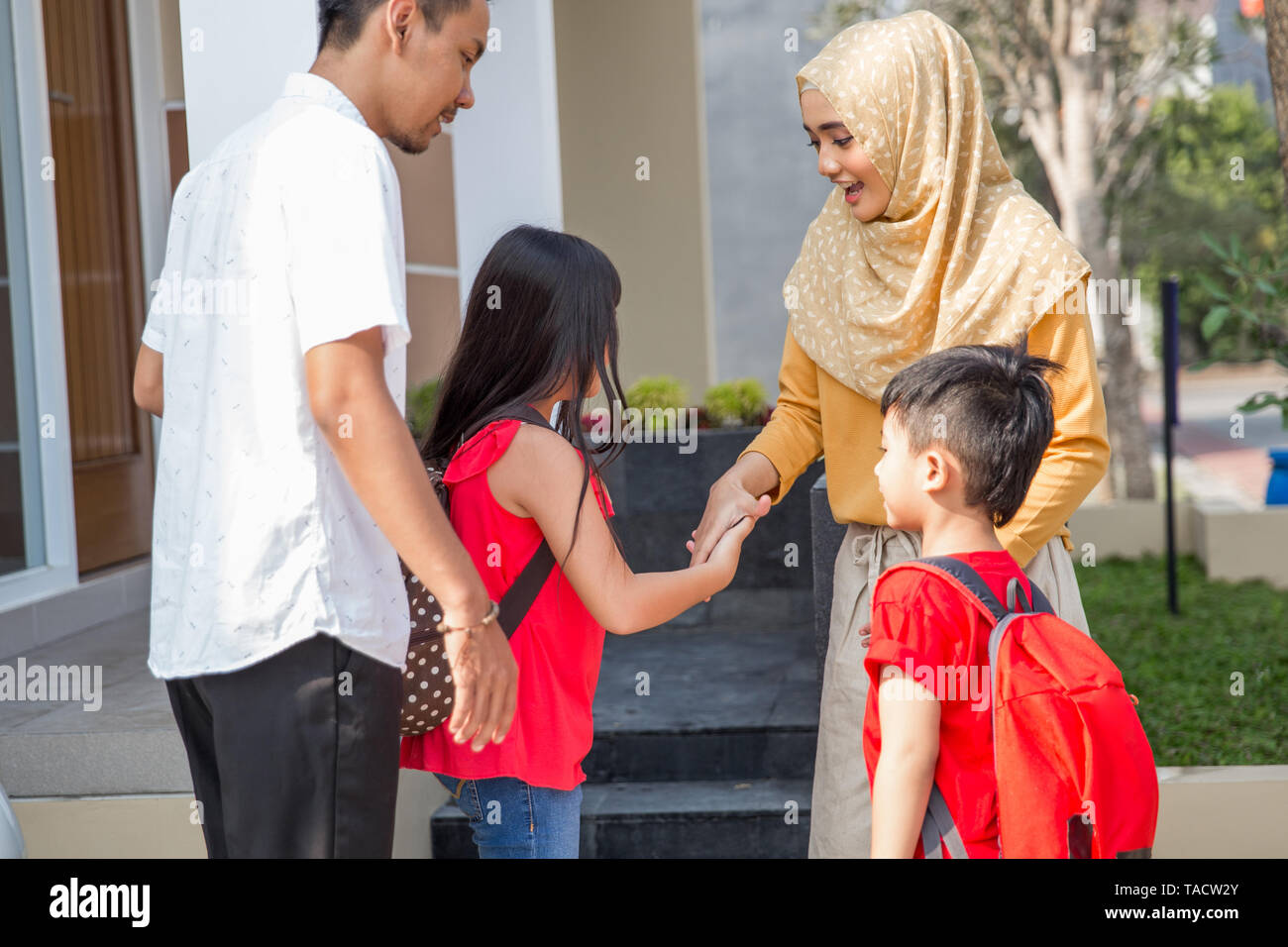 asian kid shake hand to parent before going to school in front of the house - Stock Image