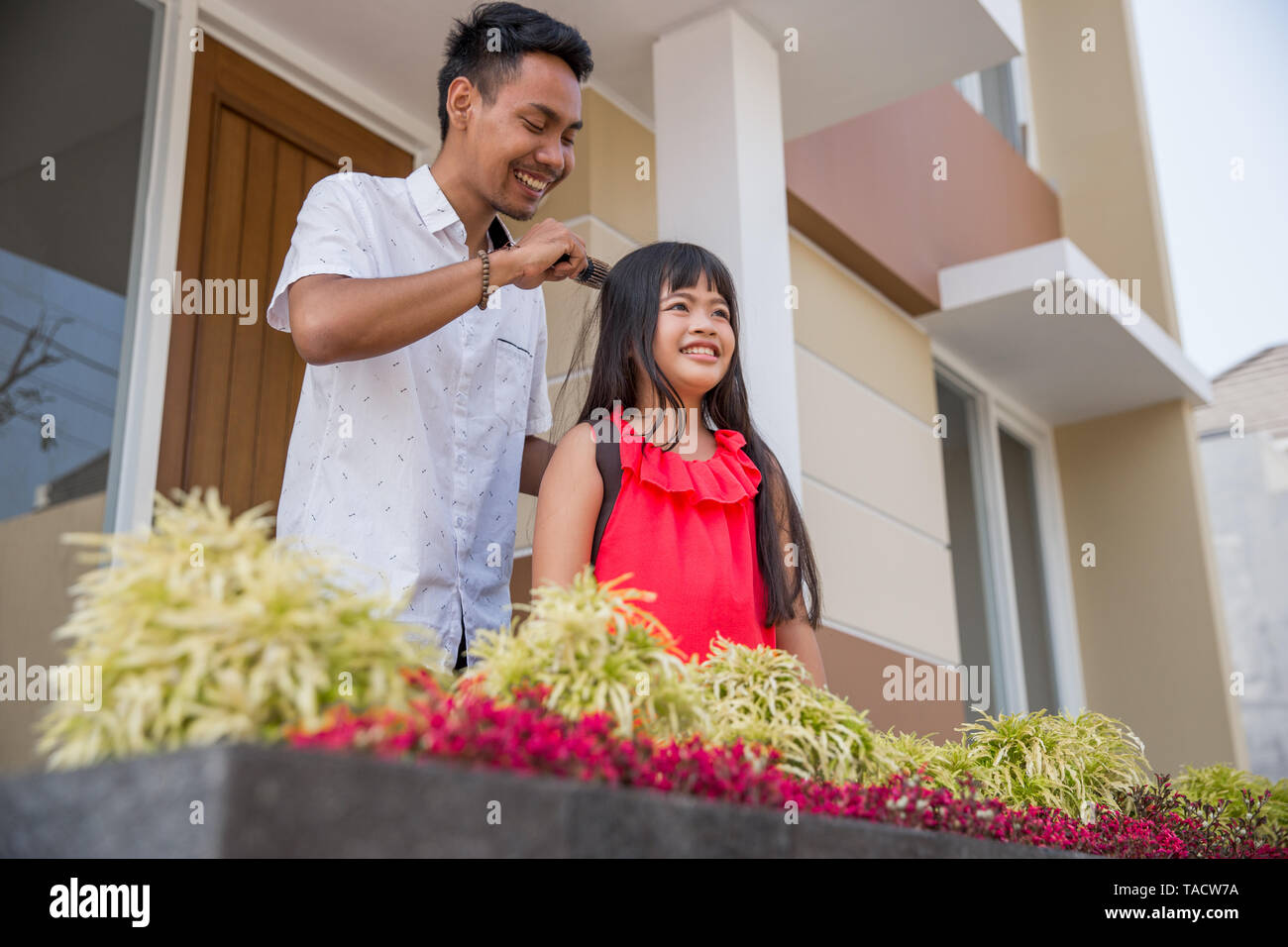 portrait of dad help her daughter to comb her hair at home - Stock Image