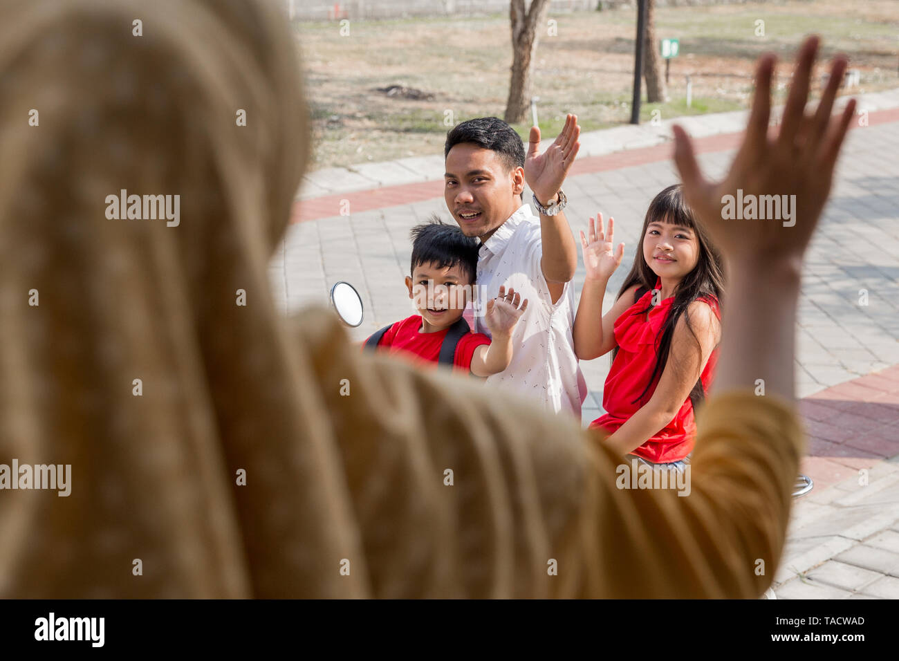 portrait of daddy taking his kids to school by motor bike waving goodbye to mommy - Stock Image