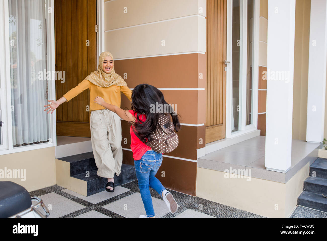 happy kid arriving home and hug mom in front of the house - Stock Image