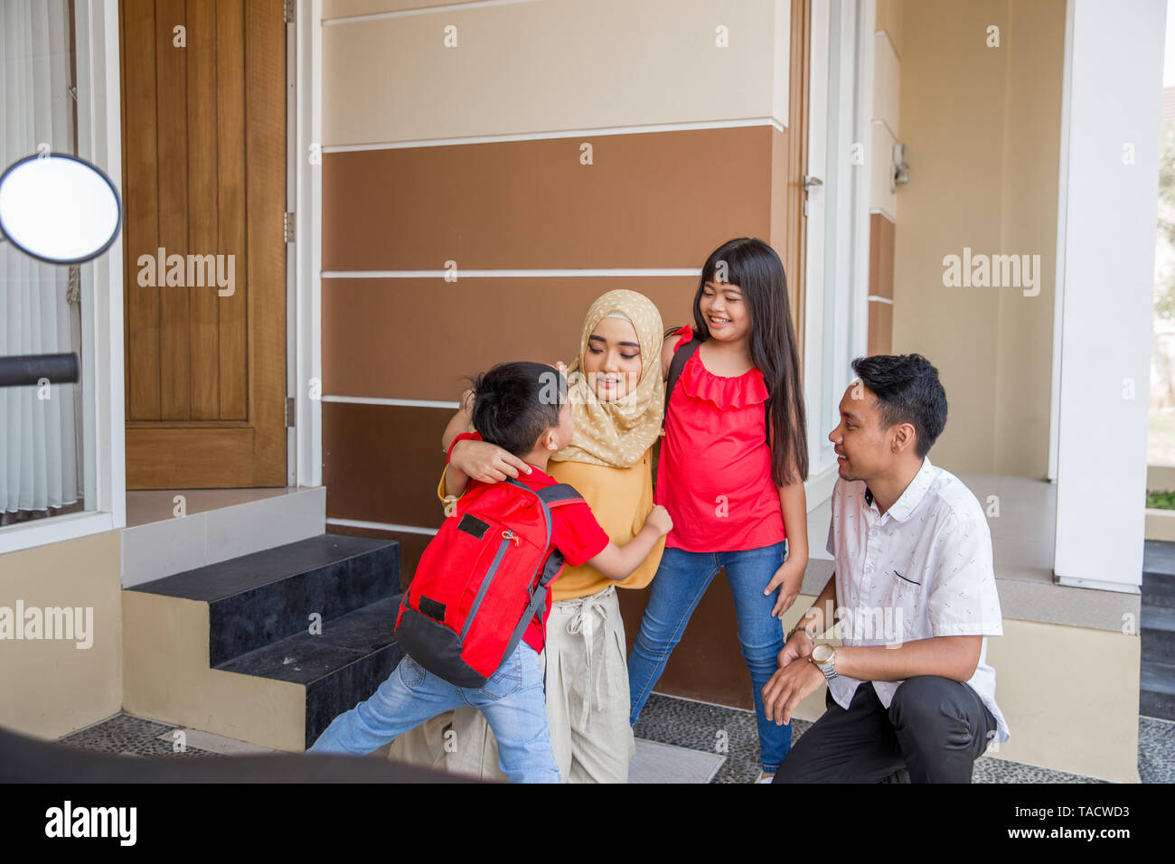 asian kid boy and girl hug their parents before going school - Stock Image