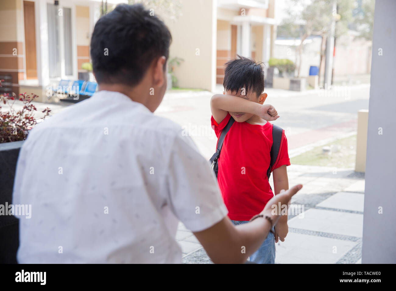 Angry father scolding son in front of the house - Stock Image
