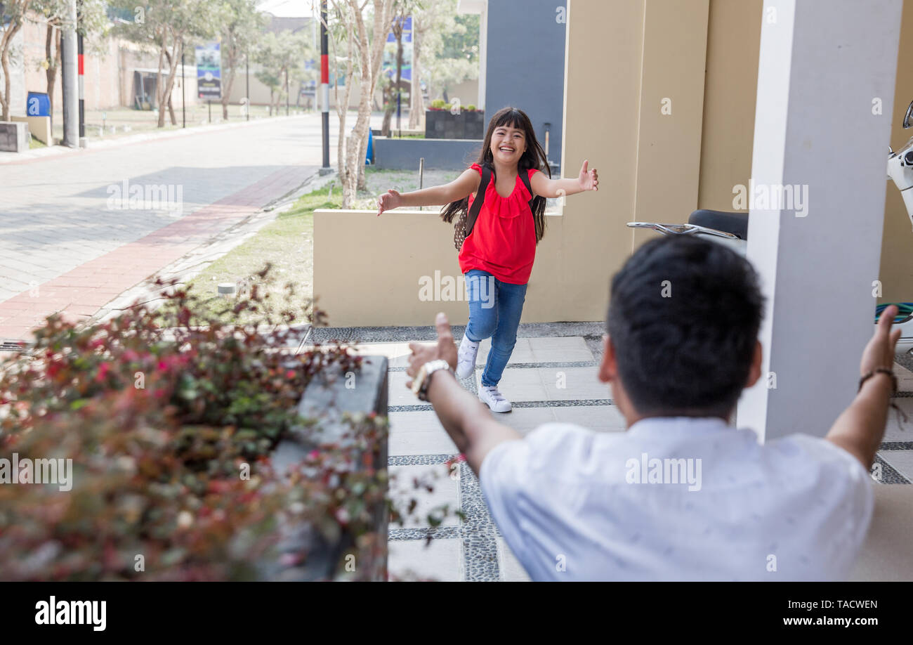daughter running and hugging dad Stock Photo