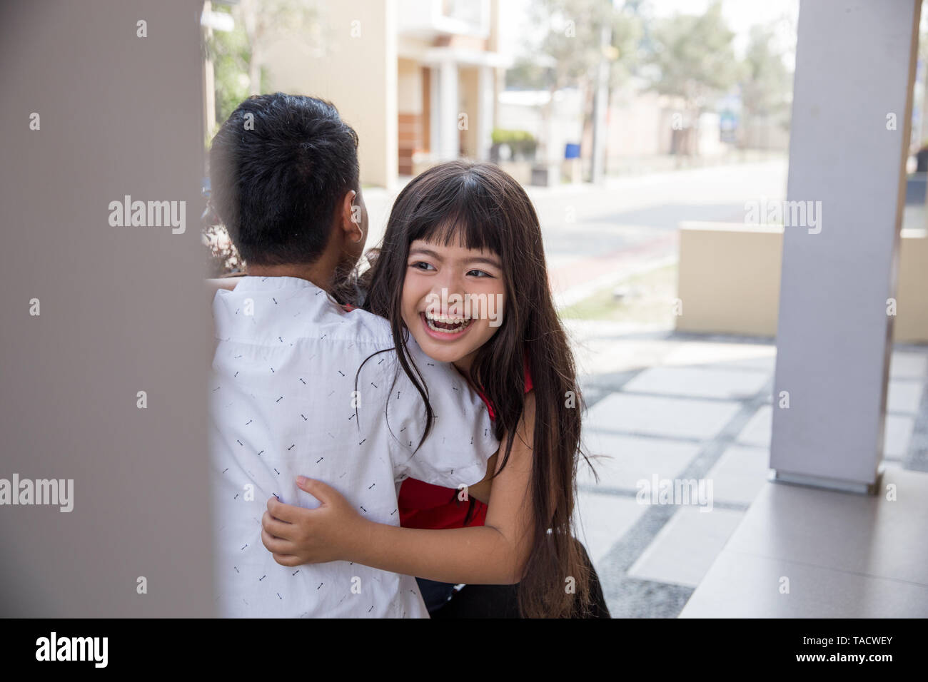 Happy family daughter running and hugging dad after going back from school - Stock Image