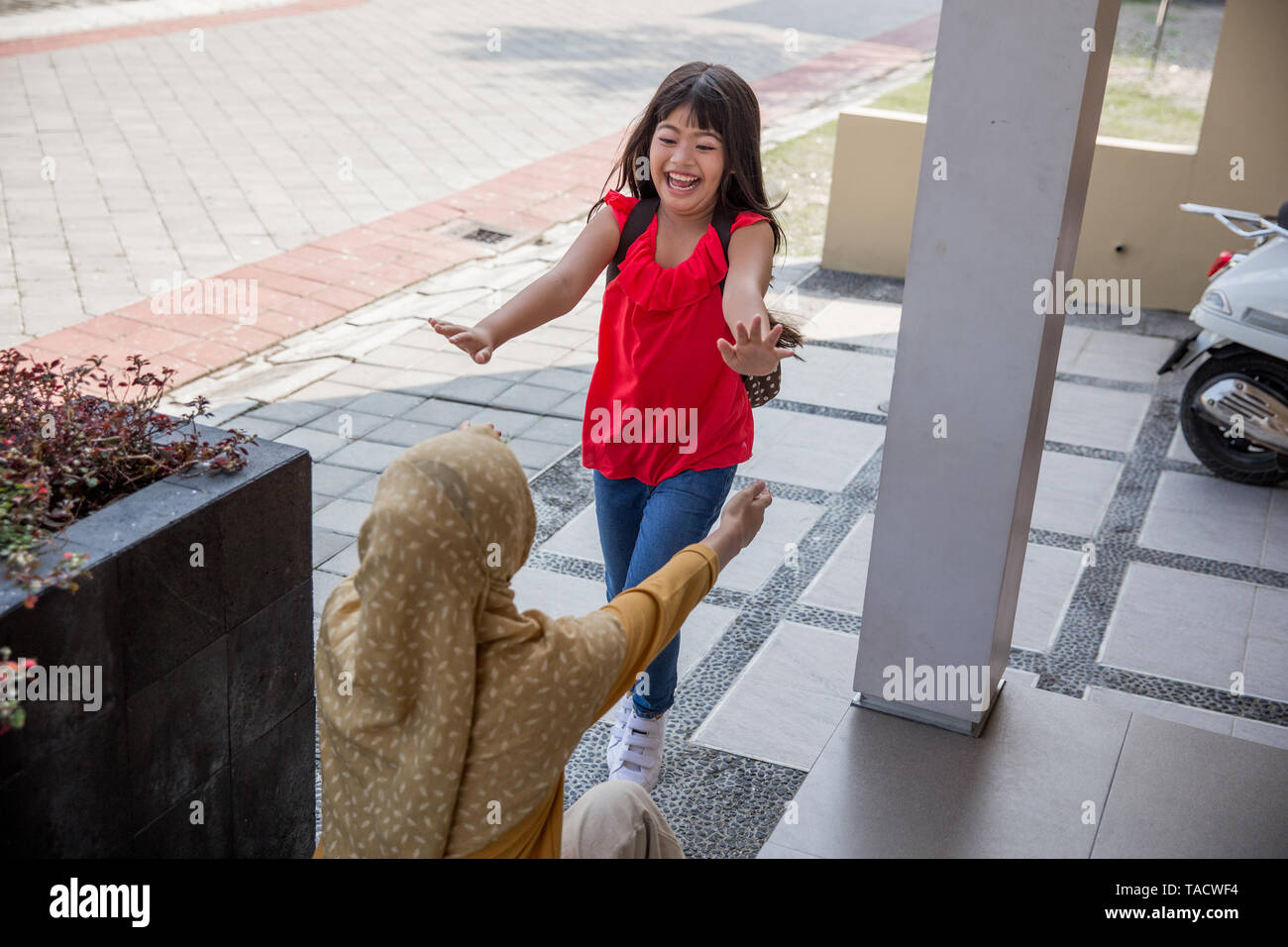 Happy family daughter running and hugging mum after going back from school - Stock Image