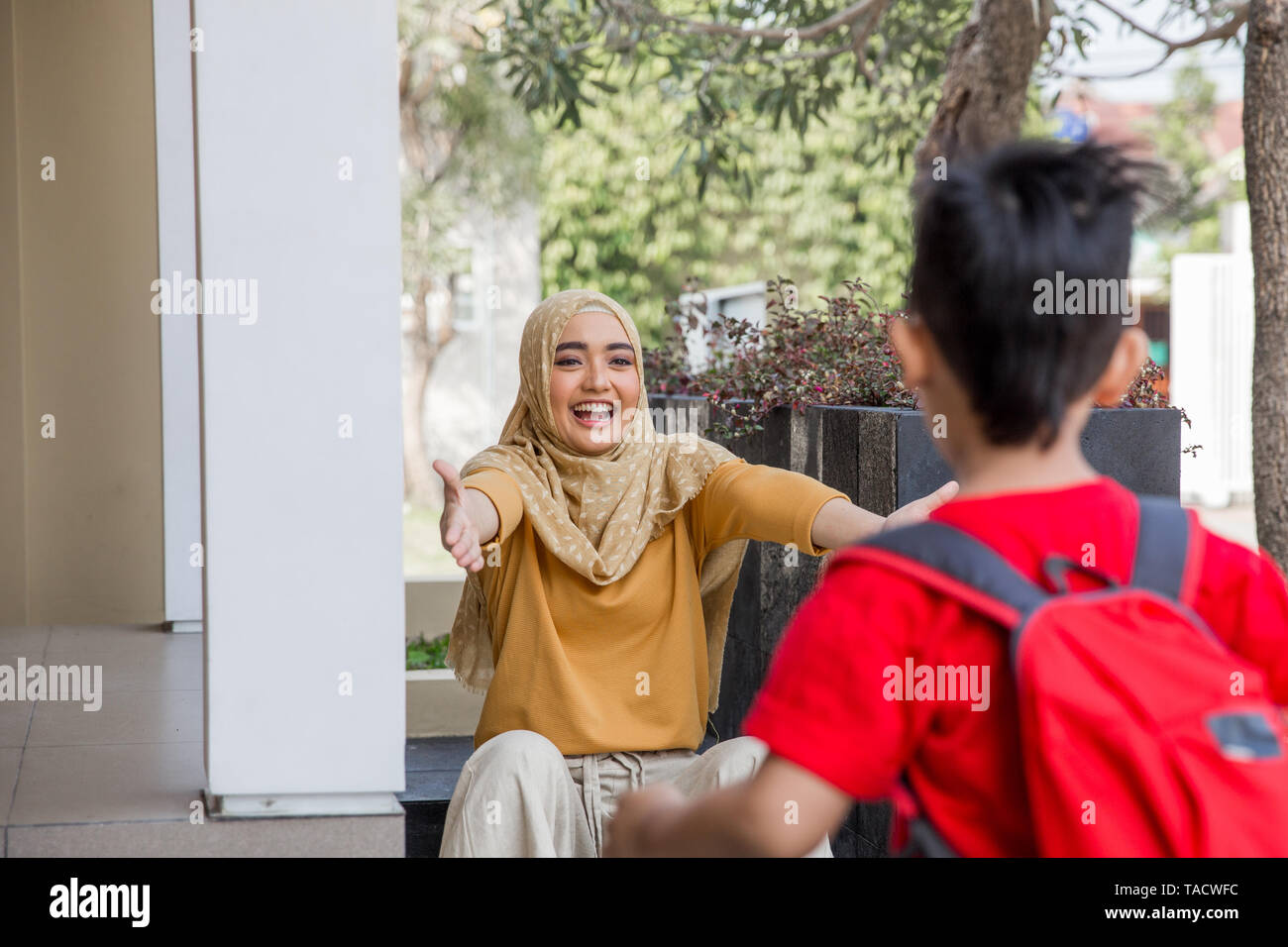 Happy family son running and hugging mother after going back from school - Stock Image