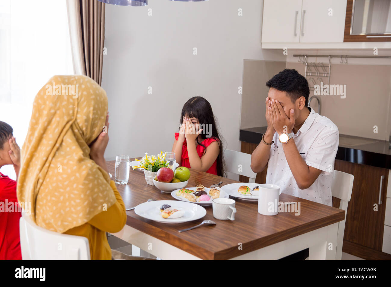 happy asian muslim family praying before having a meal together at home - Stock Image