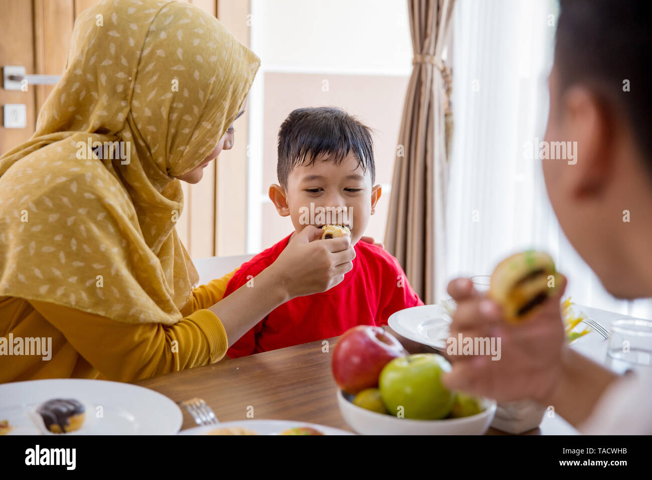 muslim mother feeding her little boy at home - Stock Image