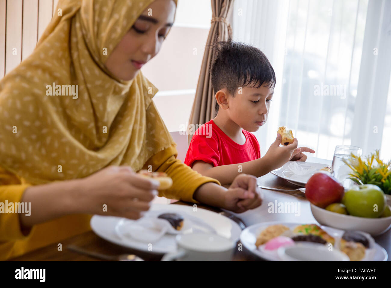 portrait of young muslim mother having breakfast with family - Stock Image