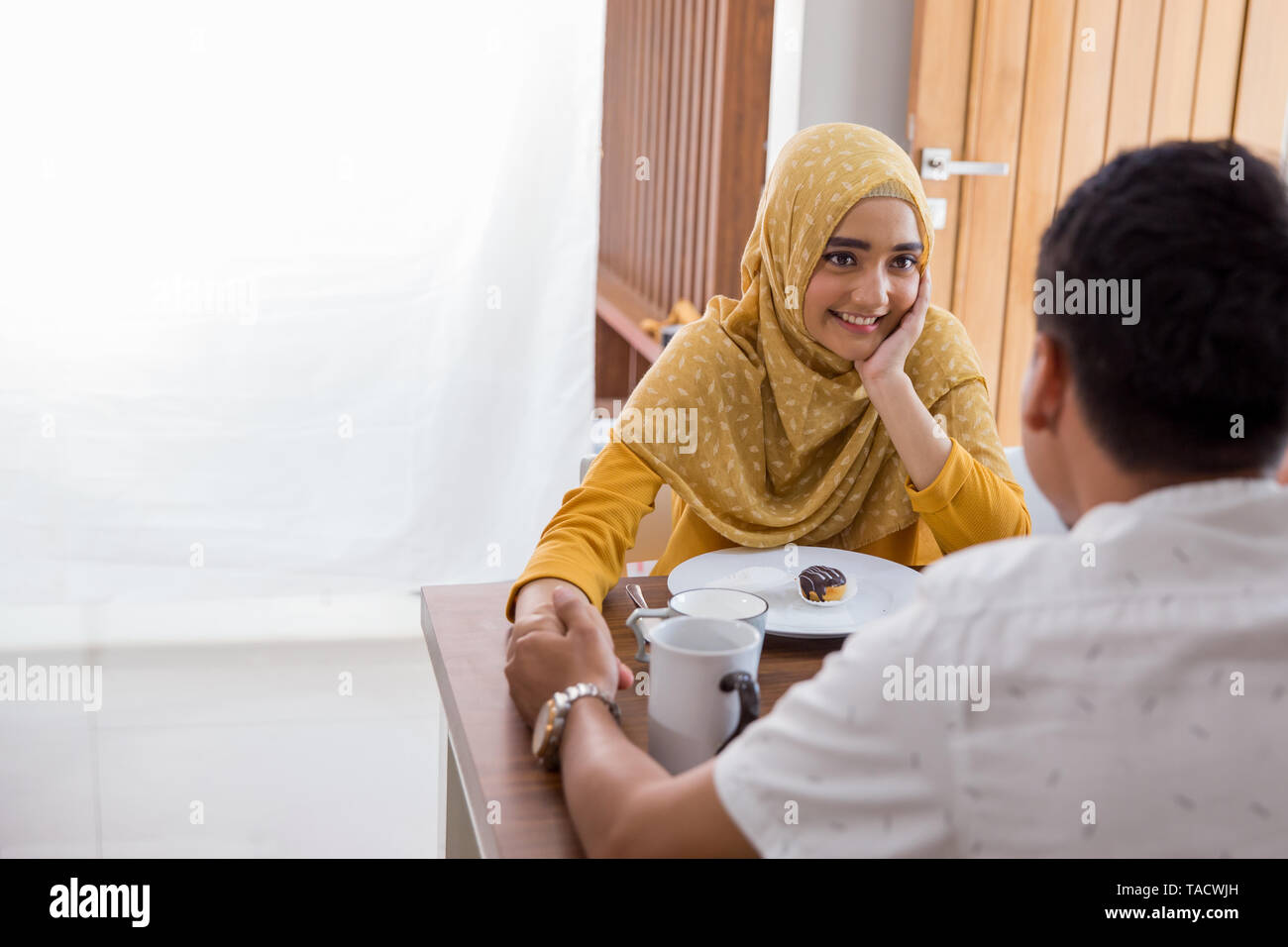 happy mother and father holding hand while having breakfast at home with family - Stock Image