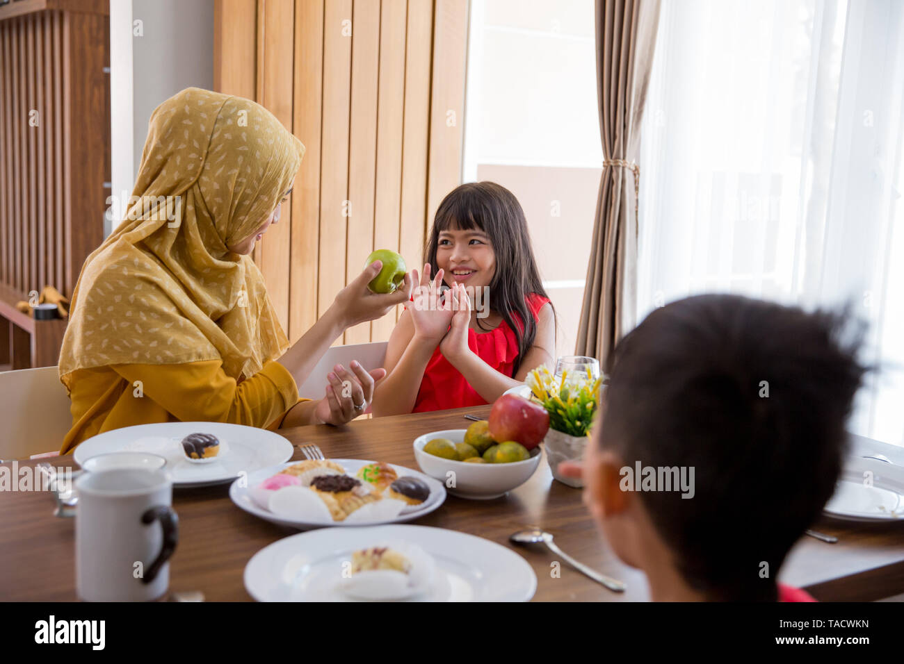 daughter refuse when mother try to offer some healthy food in living room - Stock Image
