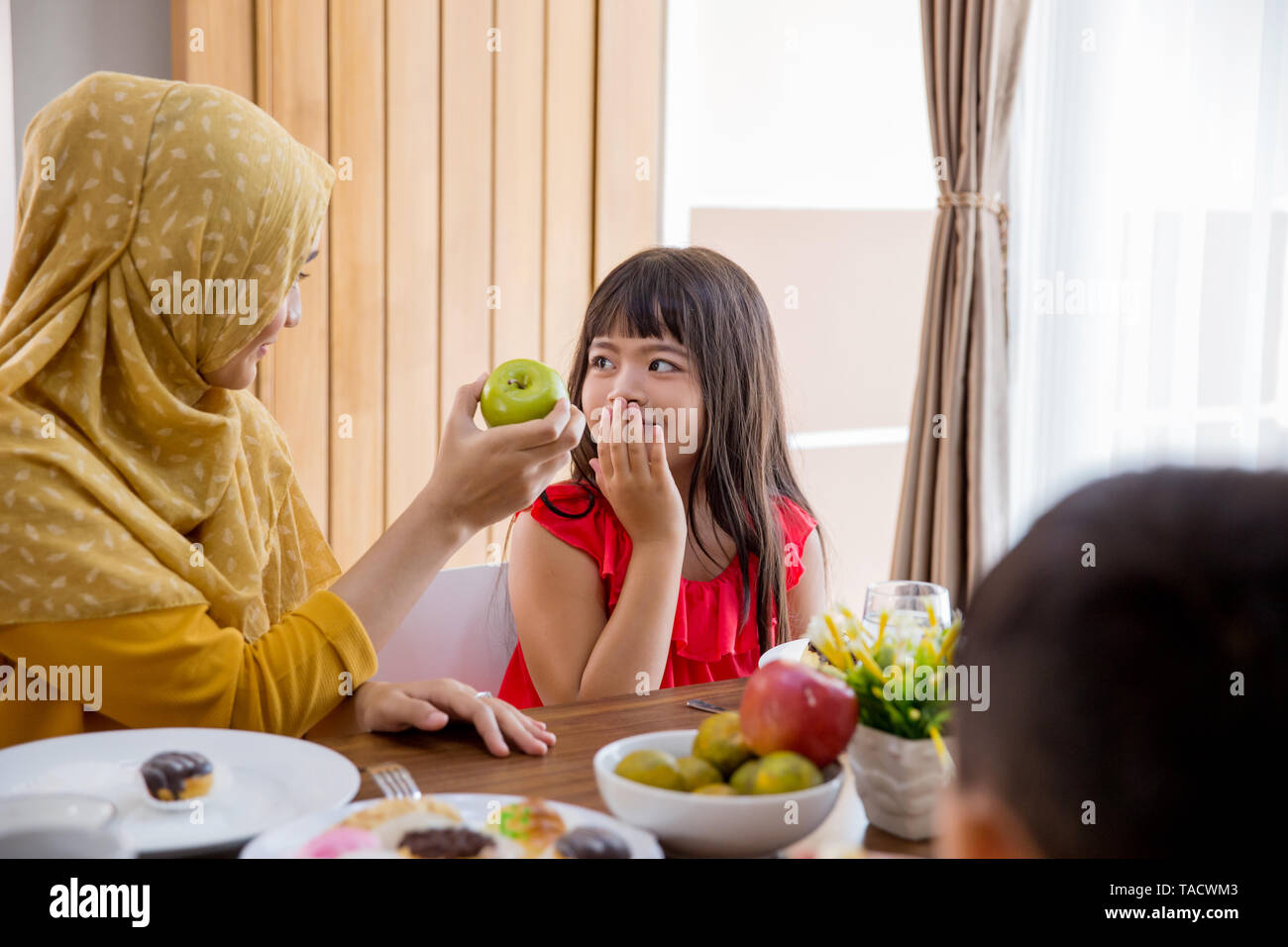 daughter refuse to eat apple Stock Photo