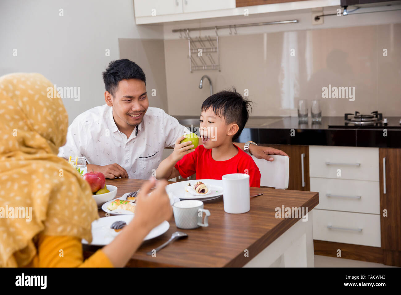 portrait of a boy eating apple in breakfast with parent - Stock Image