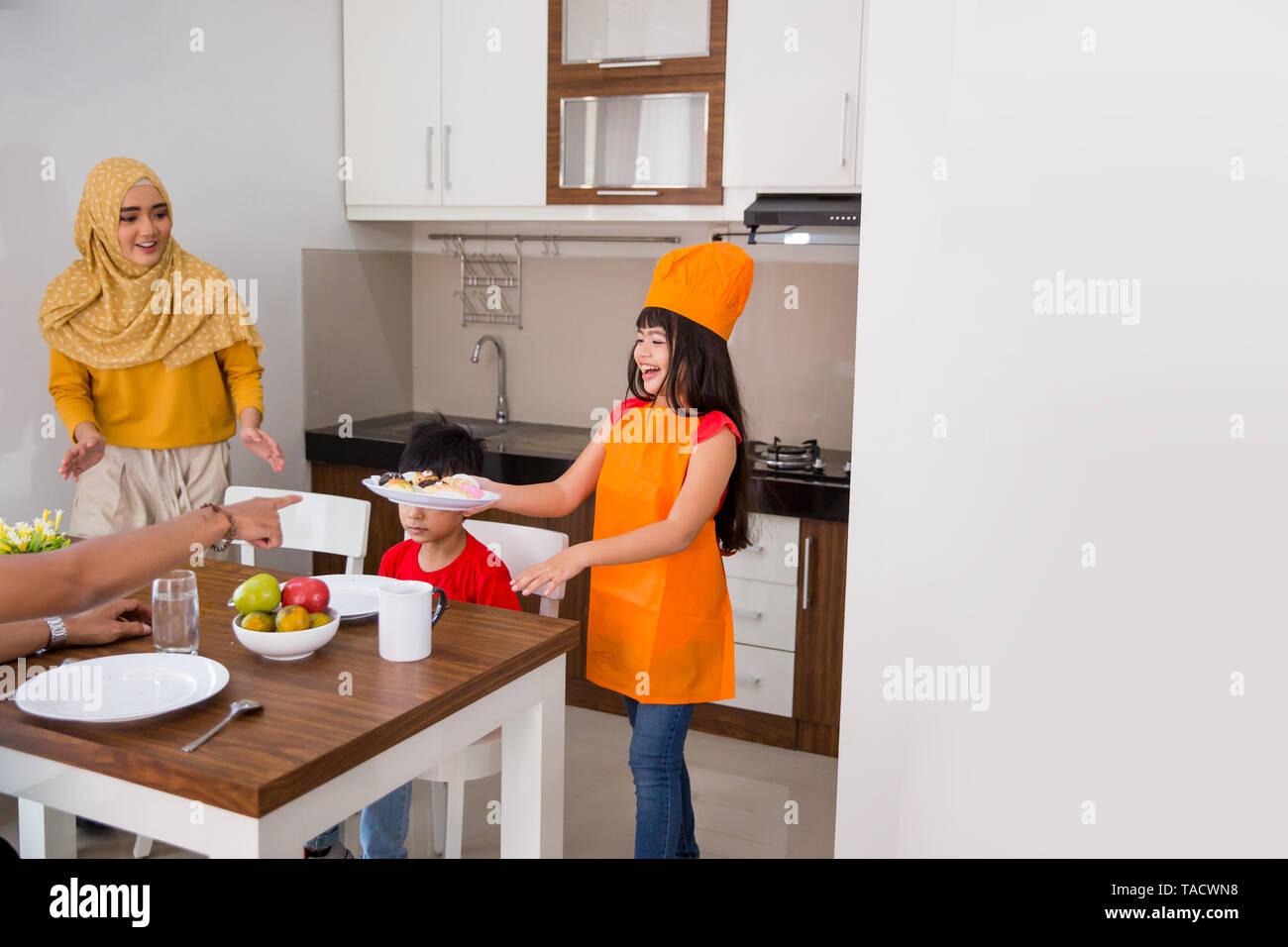 beautiful daughter help mom preparing food for breakfast - Stock Image
