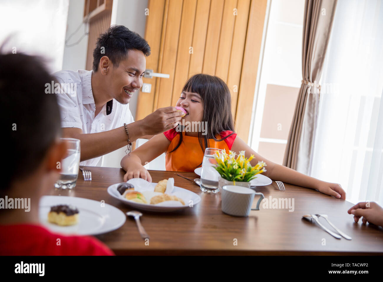father feed daughter during family breakfast at home - Stock Image