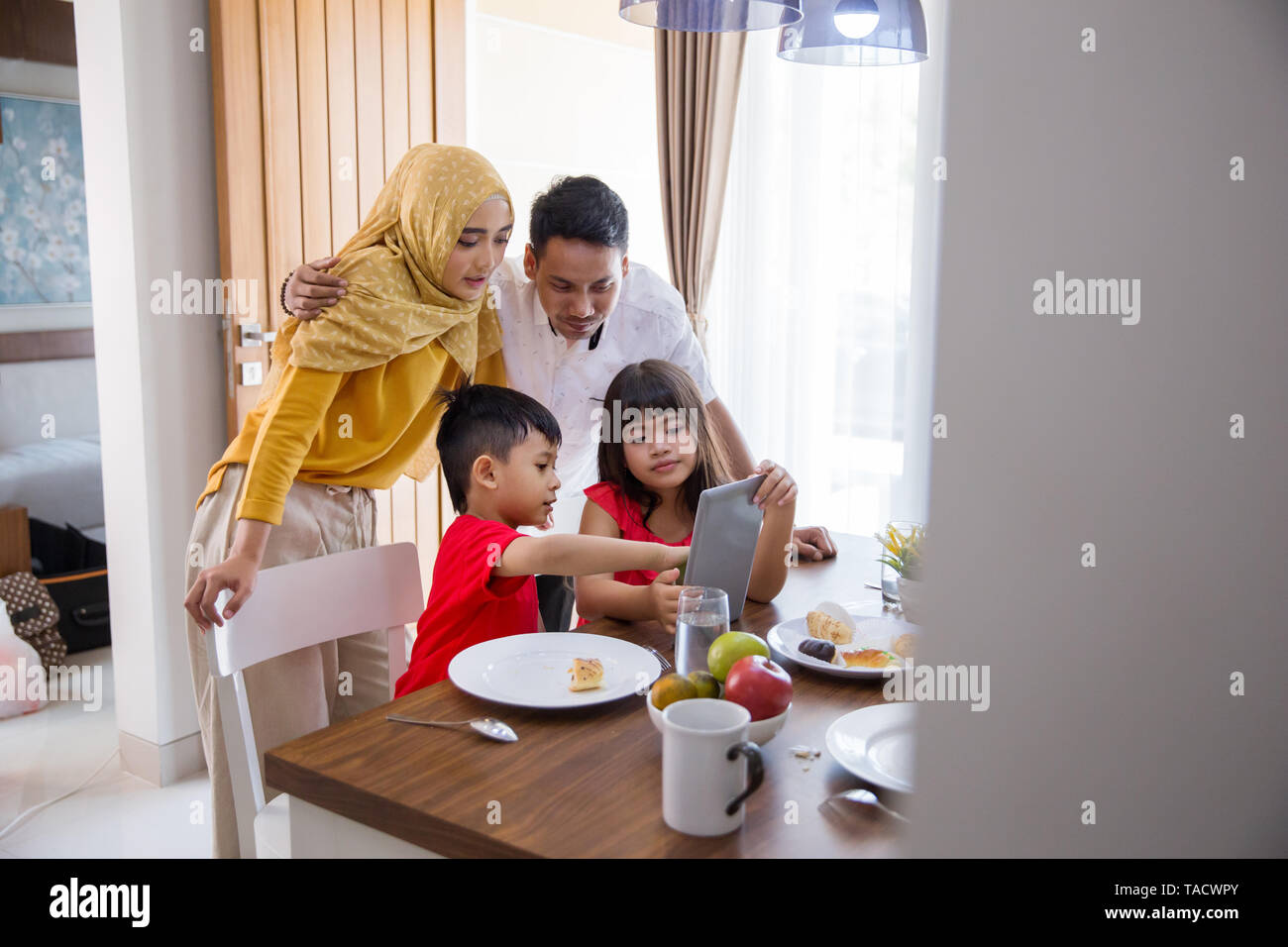 asian family using tablet pc at home during breakfast in the morning - Stock Image
